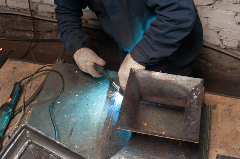 Blacksmith soldering metal plates