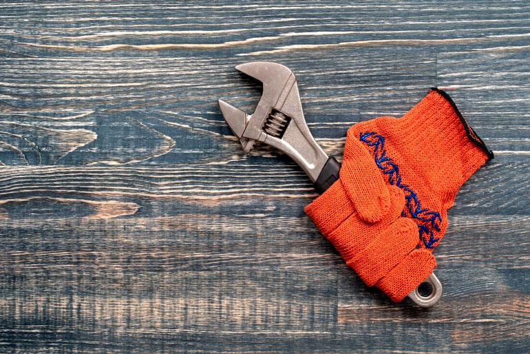 Orange construction gloves and monkey wrench