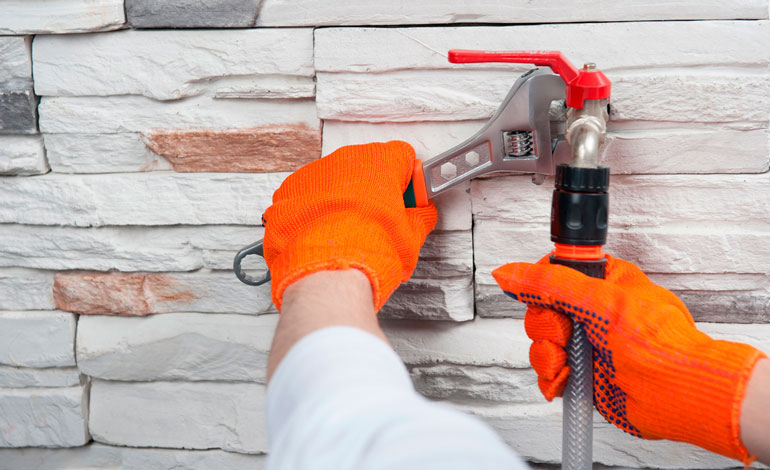 Plumber in orange gloves mounting a flexible pipe