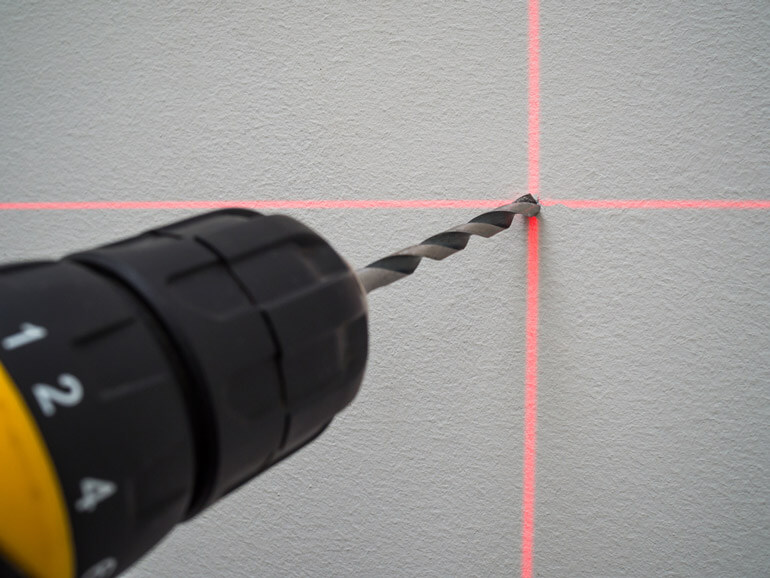 drill in the center of laser cross on the wall