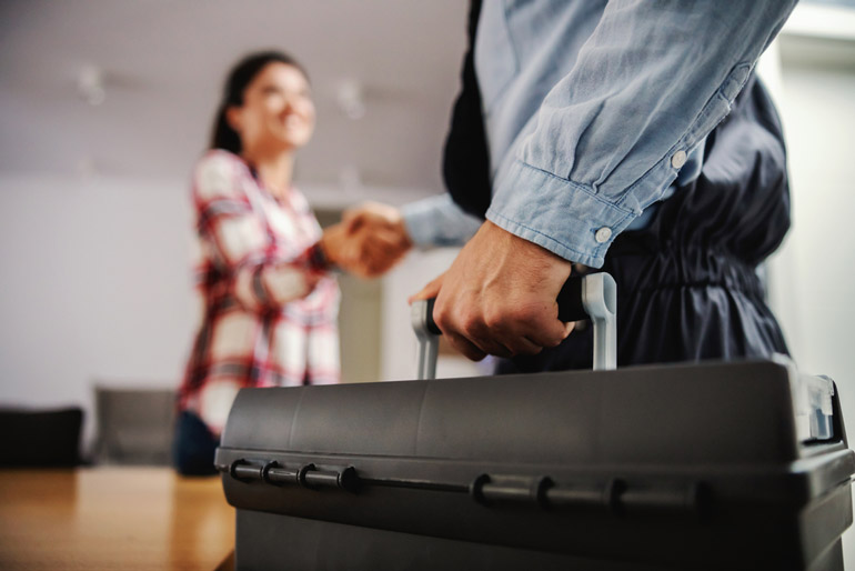 Woman shaking hands with repairman