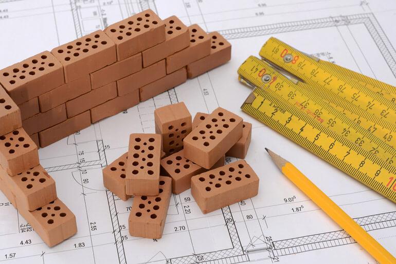 bricks pencil ruler on blueprints