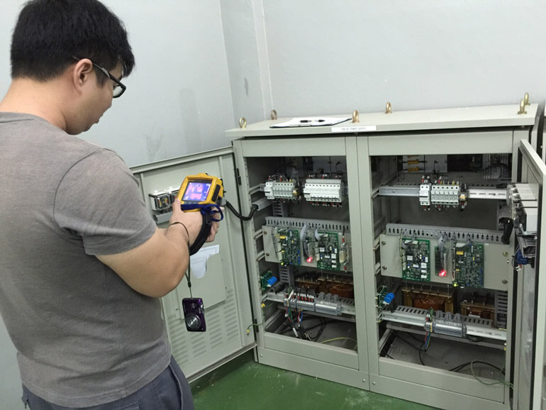 engineer checks temperature of electrical cabel
