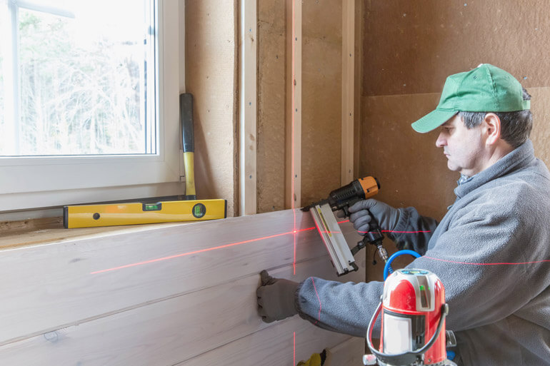 man drills with laser level