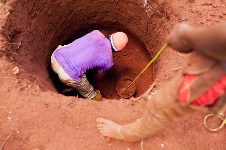 young boys manually digging well